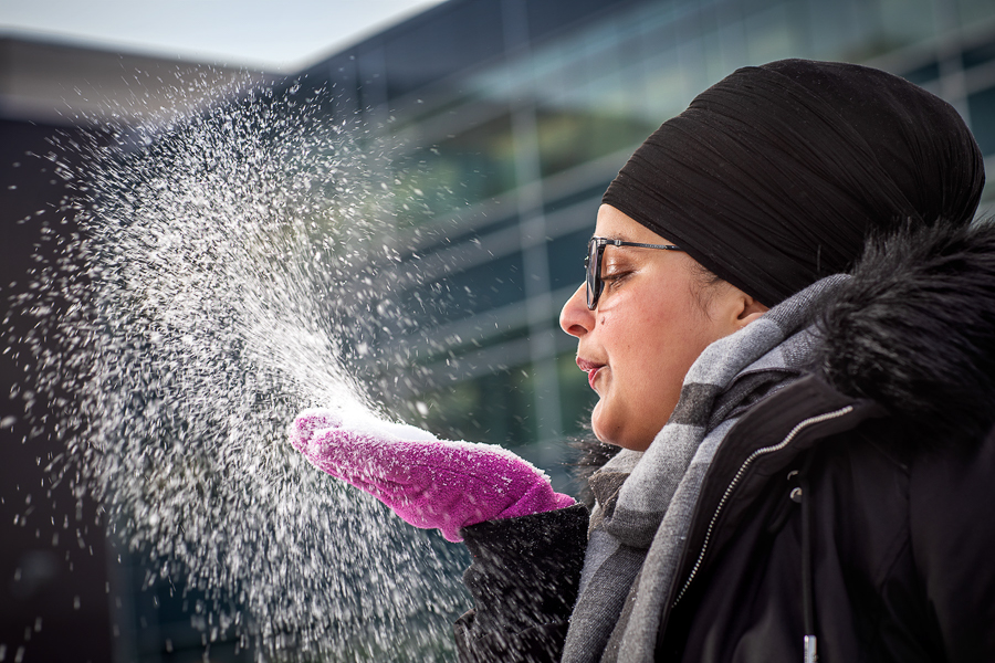 Student blows snow from her hand