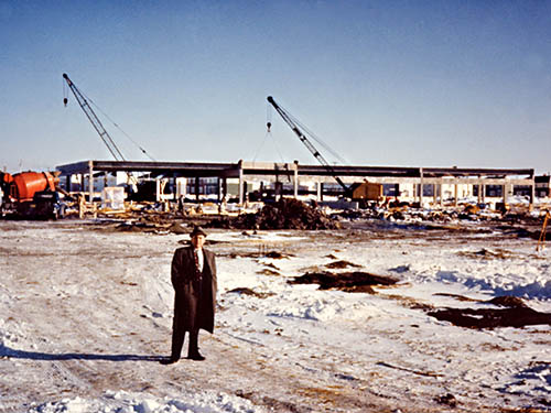 NAIT principal Jack Mitchell in front of construction of Main Campus, 1962