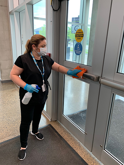 cleaning staff sanitizing doors