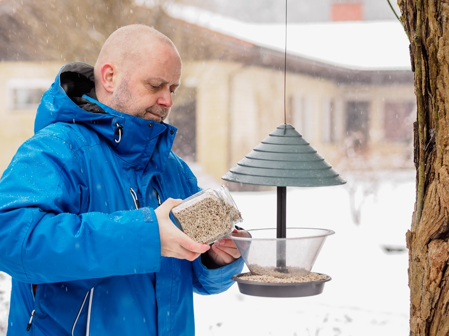 man filling bird feeder