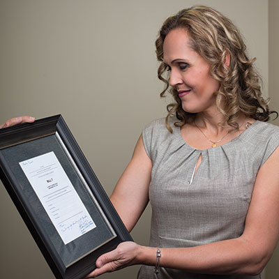 Marni Panas with a copy of Bill 7 signed by Kathleen Ganley, minister of justice and solicitor general. Panas helped write the language for the bill.
